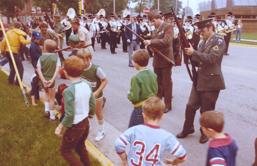 Kids scramble for empty blank shell casings during Memorial Day ceremonies in Kaukauna in 1984. Dan Plutchak photo.