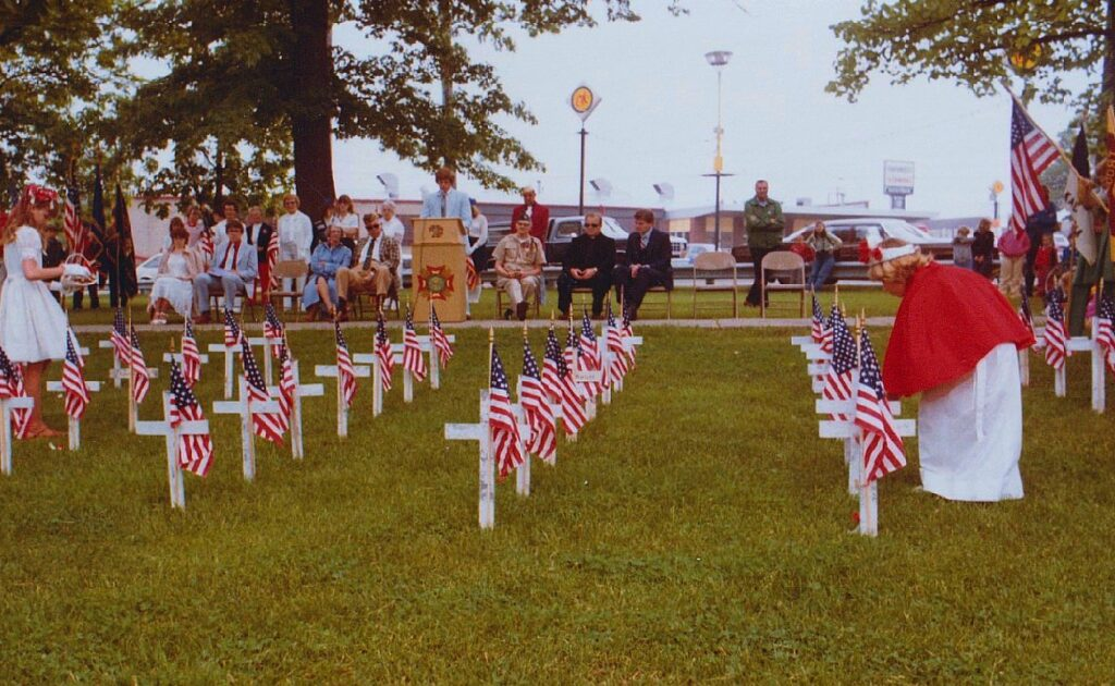 Poppy Princesses place flags to the fallen during a 1984 Memorial Day ceremony in Kaukauna. Photo by Dan Plutchak.